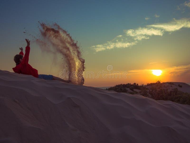 Tonad bild av lite pojken i kortslutningar och omslaget, som ligger på en sanddyn och att kasta upp sanden på en bakgrund av färg royaltyfria foton