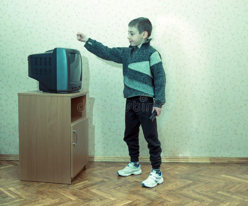 Tonad bild av lite pojken med en besviken framsida som rymmer TV:N avlägsen royaltyfri fotografi