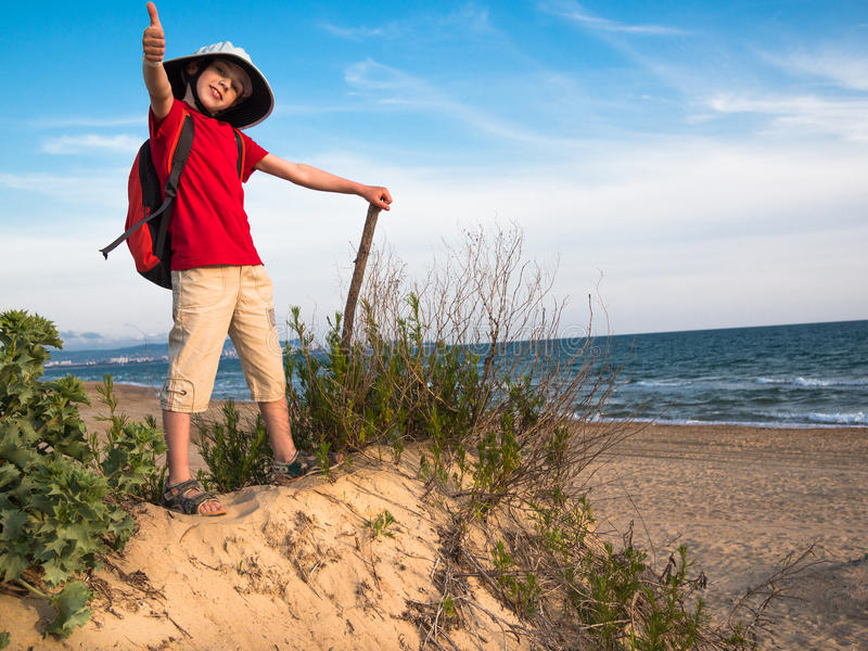 Tonad bild av lite pojken med en ryggsäck och en hatt som rymmer pinnen och anseendet på en sandig kulle och le mot lodisarna arkivfoton