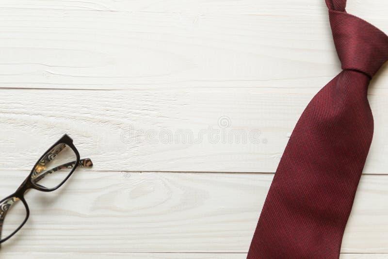 Tonad bild av slipsen och glasögon som ligger på vit träbaksida arkivfoto