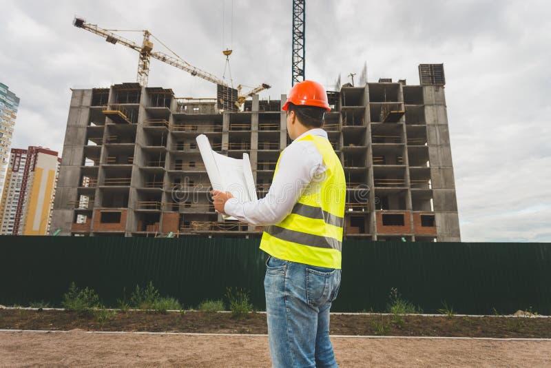 Tonad bild av teknikern i hardhaten som kontrollerar byggnadsplatsen arkivfoton