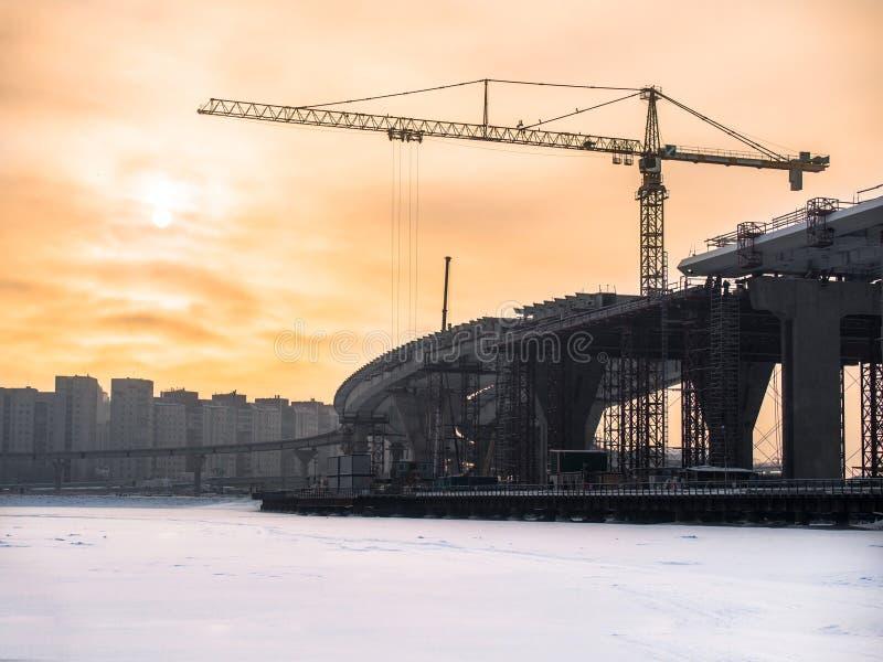 Tonad bild under konstruktionsvägbron över den djupfrysta floden med en stor tornkran mot bakgrunden av en intelligens för molnig royaltyfria foton