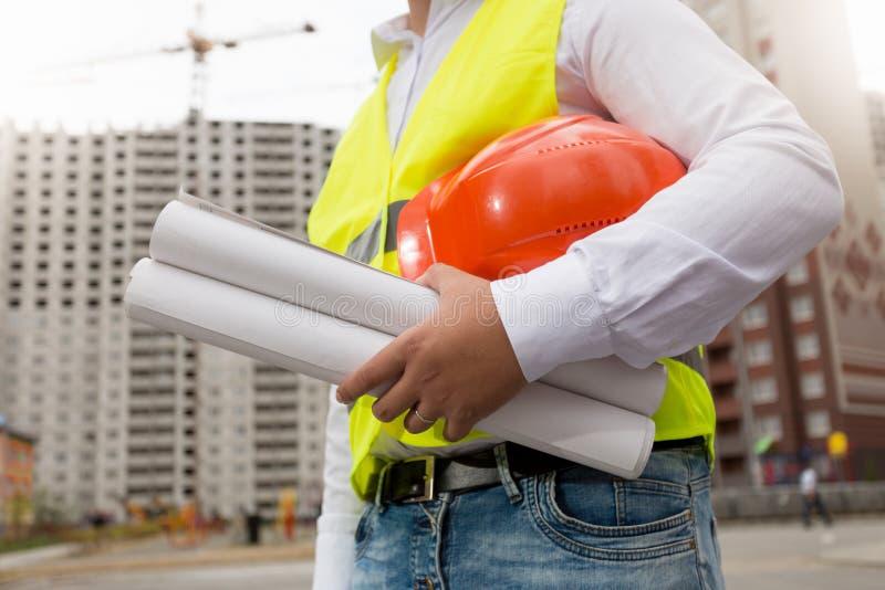 Tonad closeupbild av den unga arkitekten som poserar på byggnadsplatsen arkivbild