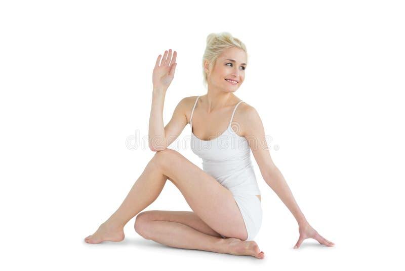 Tonad kvinna i den Ardha Matsyendrasana positionen arkivfoto
