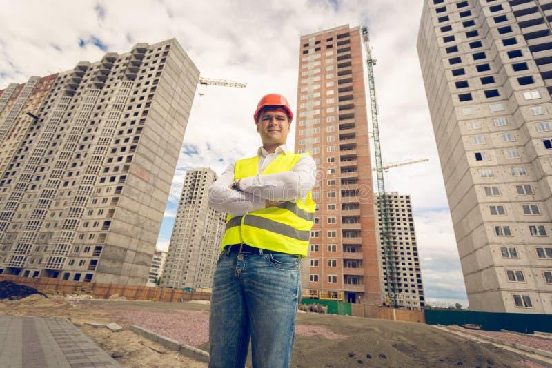 Tonad stående av att le den unga byggnadsarbetaren i hardhatanseende på byggnadsplats och att se in camera arkivbilder