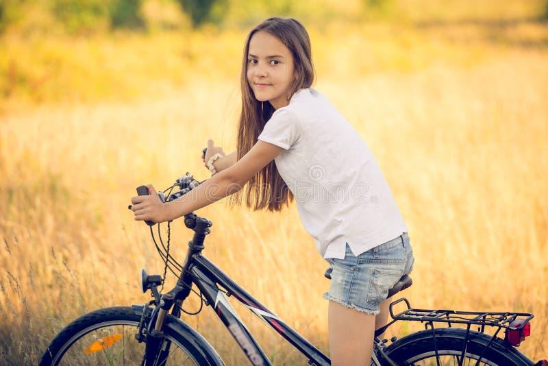 Tonad stående av den härliga flickan som poserar på cykeln på ängen på royaltyfria foton
