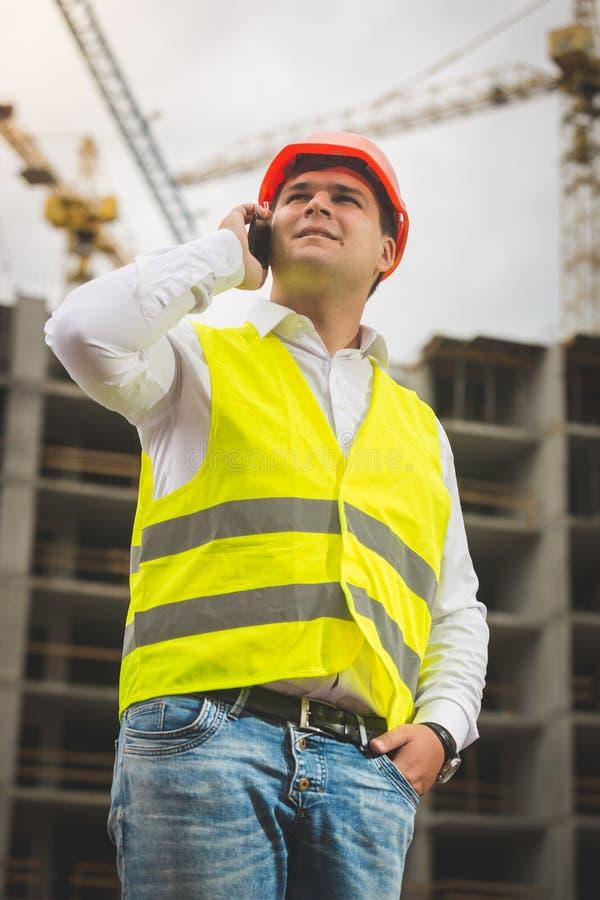 Tonad stående av den unga manliga teknikern som talar vid telefonen och ser byggnad under konstruktion fotografering för bildbyråer