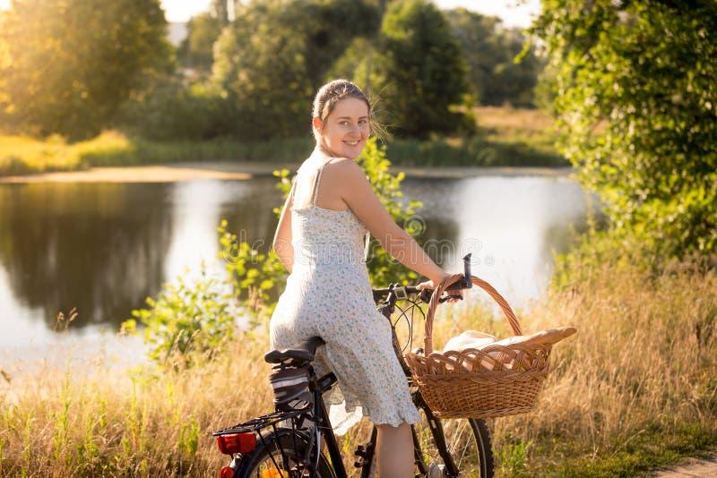 Tonad stående av kvinnan i klänningsammanträde på cykeln på sjön royaltyfri fotografi