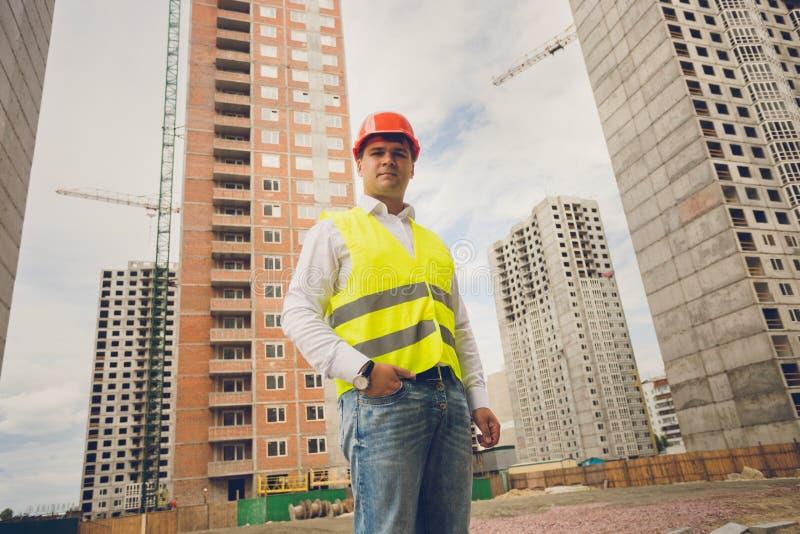 Tonad stående av teknikern som poserar mot byggnader under constr royaltyfri bild
