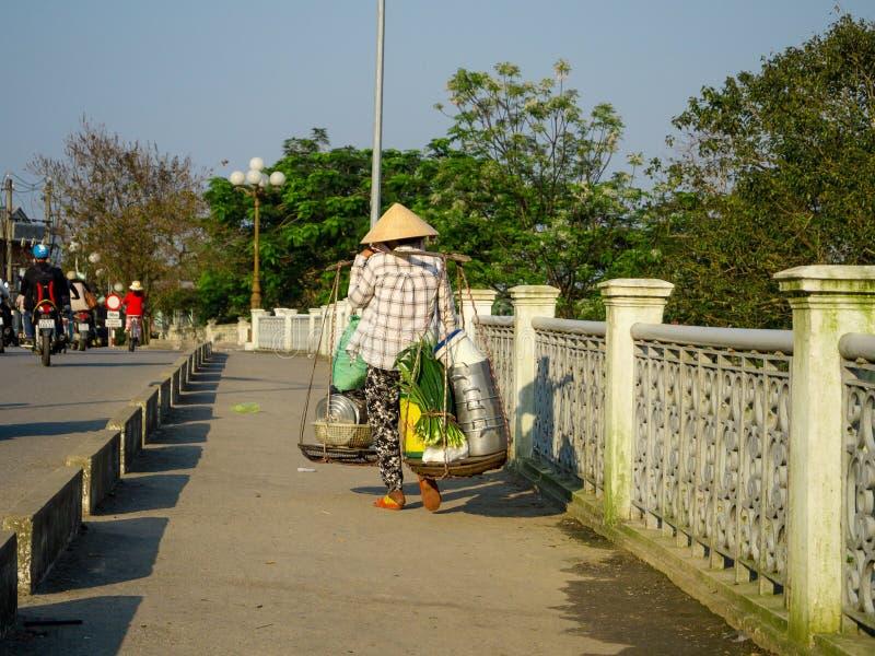 Tonalidad, Vietnam - 13 de septiembre de 2017: Mujer no identificada que cruza el puente y que lleva en sus hombros la comida en fotografía de archivo libre de regalías