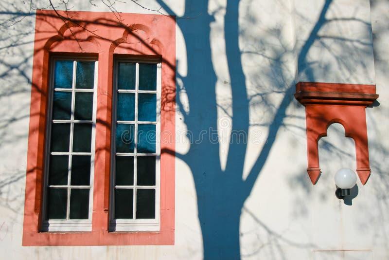 Tonalità di finestra dipinte rosse aperte di un albero sulla parete fotografie stock libere da diritti
