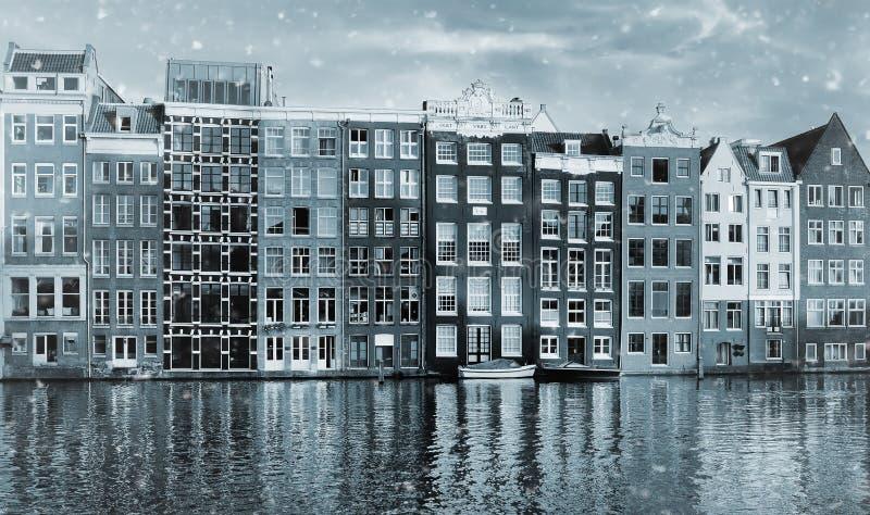 Tonat foto av berömda dansa hus av den Damrak kanalen i Amsterdam på solnedgång royaltyfri fotografi