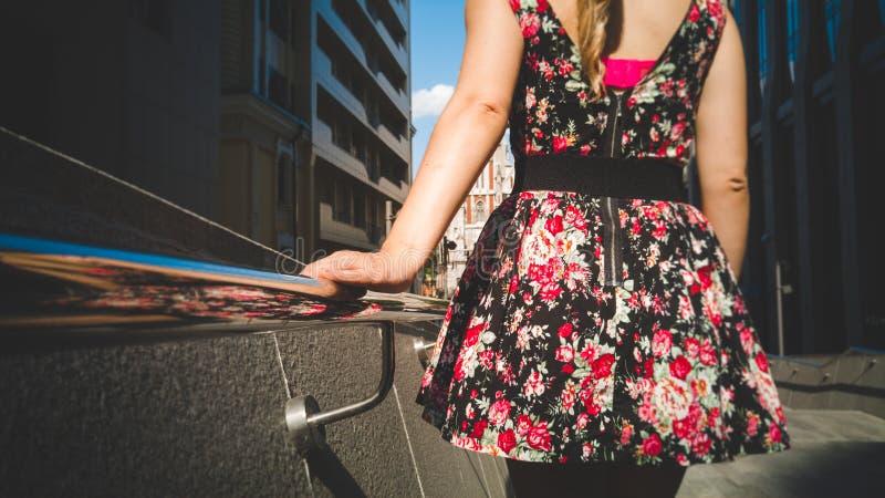 Tonat foto av den härliga unga kvinnan i kort klänning med det blom- trycket som går ner trappan på stret och rymmer handen royaltyfri foto
