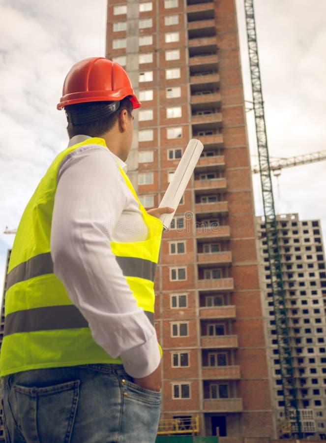 Tonat foto av konstruktionsteknikern som under pekar på byggnad royaltyfria foton