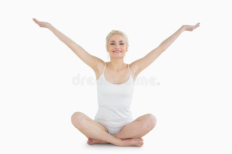 Tonat sammanträde för ung kvinna med utsträckta armar royaltyfria foton