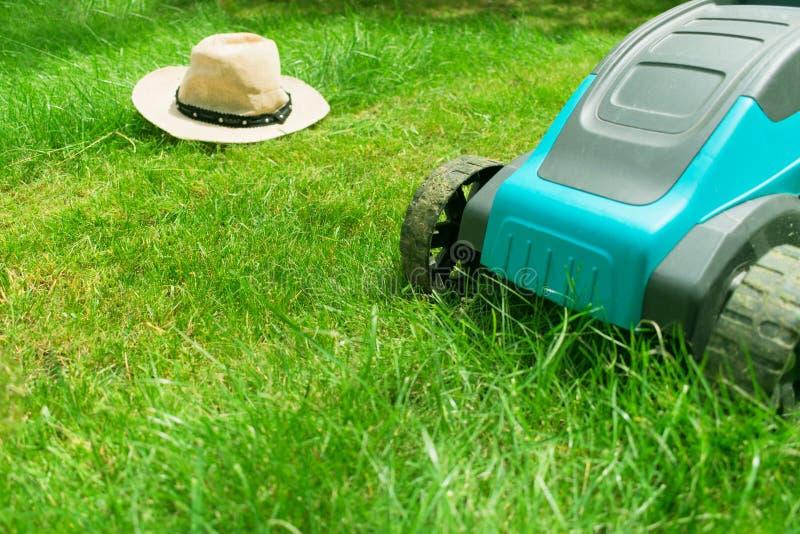 Tondeuse à gazon fauchant l'herbe verte et un chapeau de soleil Travail dans le jardin images libres de droits
