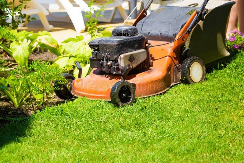 Tondeuse à gazon sur une pelouse fraîche dans le jardin photos libres de droits