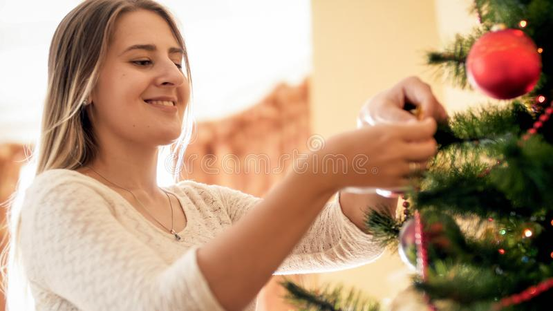 Toned closeup portrait of young woman decorating Christmas tree with baubles and beads stock photography