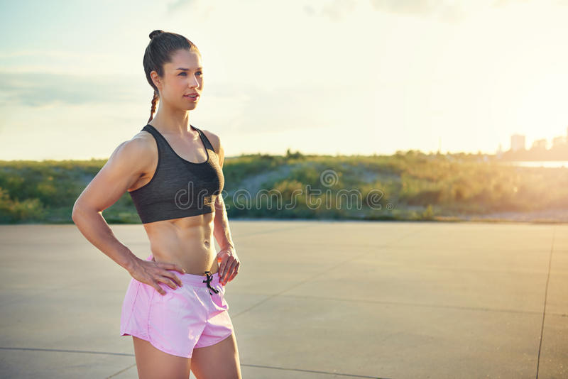 Toned healthy athletic young woman. With a strong muscular body standing with her hands on her hips outdoors in the rising sun taking a break from her workout stock image