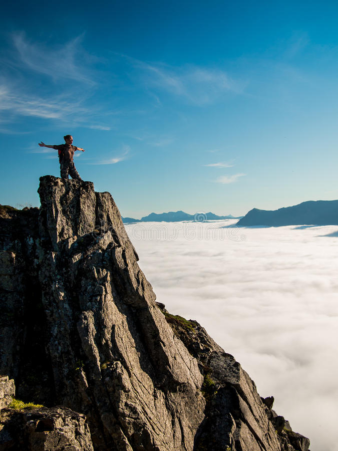 Toned image adult woman with a backpack with arms outstretched stands on the edge of a cliff and looking at the sunrise against th. E blue sky and thick clouds royalty free stock photography