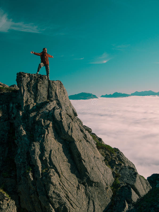 Toned image adult woman with a backpack with arms outstretched stands on the edge of a cliff and looking at the sunrise against th. E blue sky and thick clouds royalty free stock photo