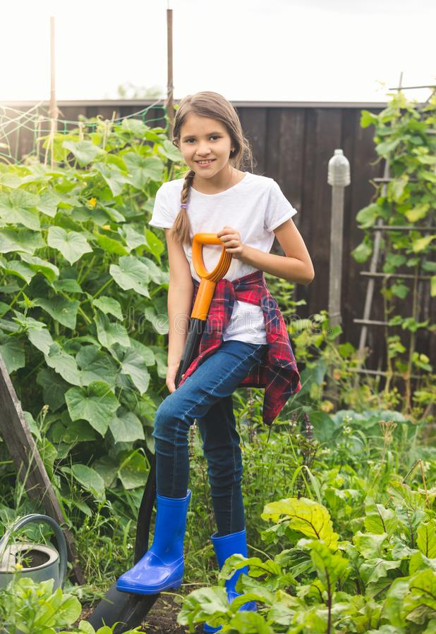 Toned photo of beautiful teenage girl digging soil in garden with spade stock photography