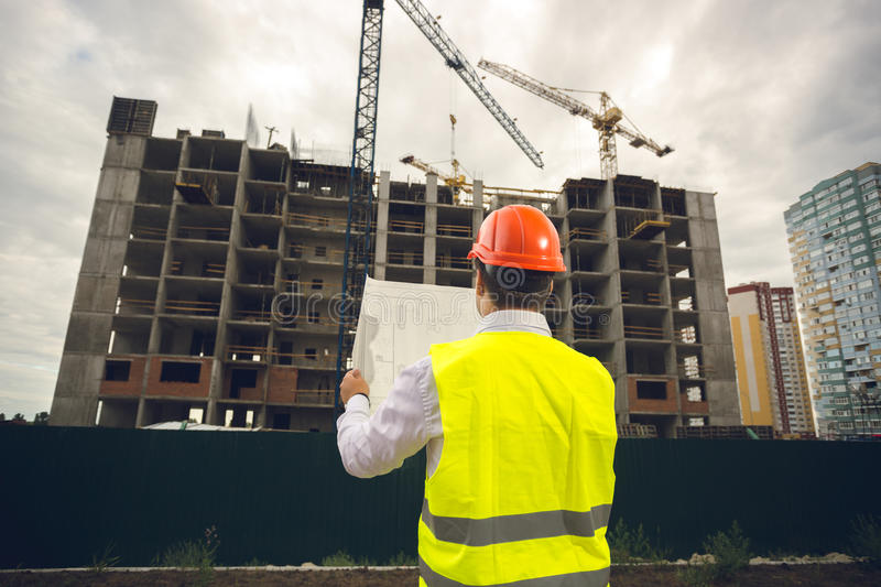 Toned image of construction engineer reading blueprints at build royalty free stock photo