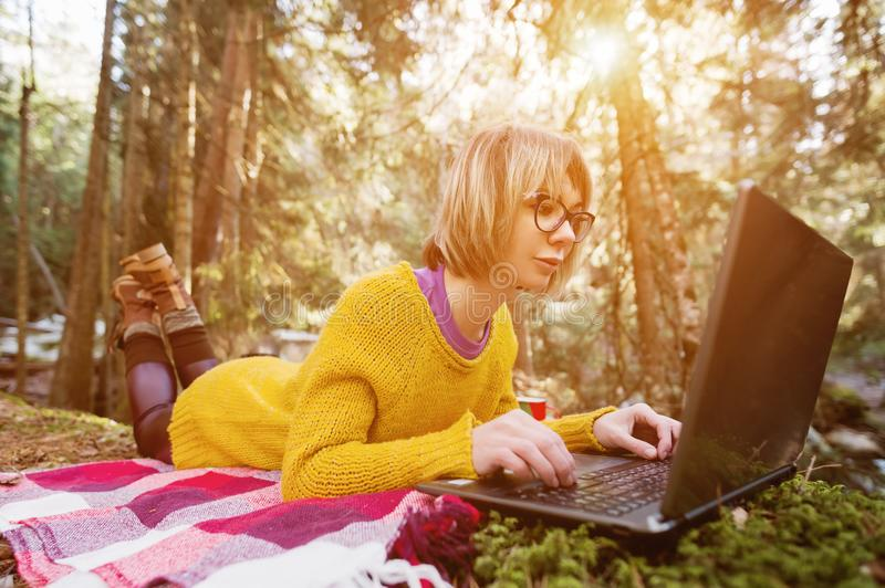 Toned image of a freelancer girl portrait in a yellow sweater and glasses looking thoughtfully at the laptop screen in stock photo