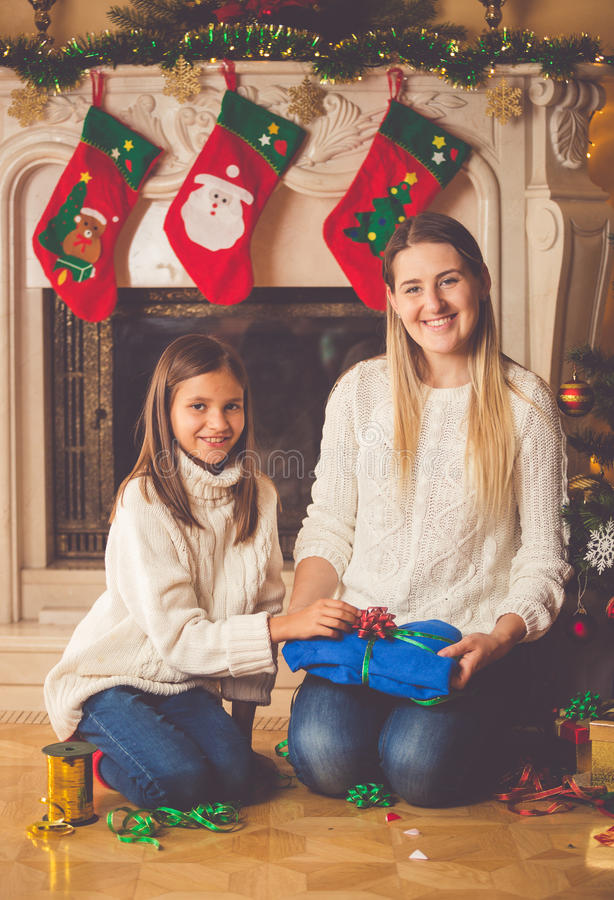 Toned image of happy mother and daughter packing Christmas presents on floor at living room royalty free stock photography