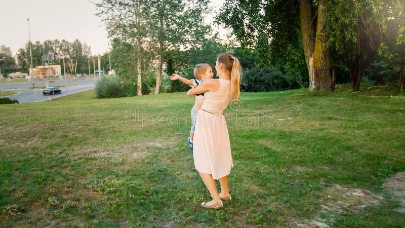 Toned image of happy smiling young mother holding and embracing her toddler son at park royalty free stock photography