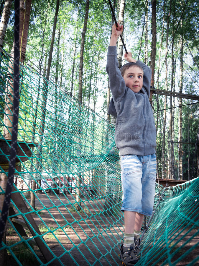 Toned image little boy with a strained face goes on a rope. On the background of the forest royalty free stock images