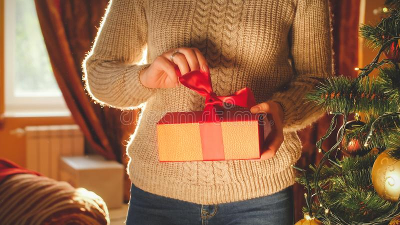 Toned image of young woman unwrapping and opening Christmas gift box. Toned photo of young woman unwrapping and opening Christmas gift box stock image