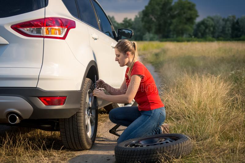 Toned image of young woman using tools to unscrew nuts on broken wheel of her car. Toned photo of young woman using tools to unscrew nuts on broken wheel of her stock image