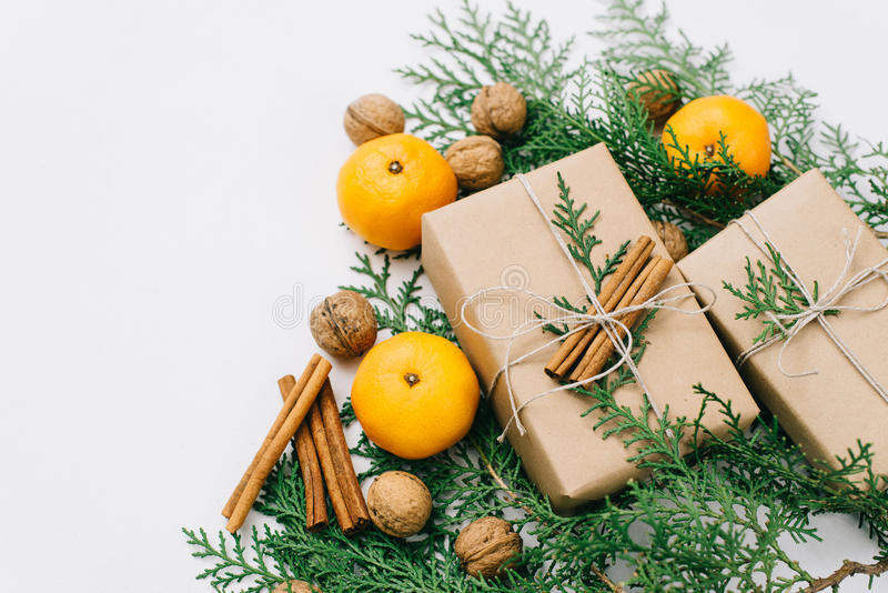 Toned instagram image wrapping rustic eco Christmas gifts with craft paper, string, tangerines and natural cypress branches on. White background Flat lay, free royalty free stock photography