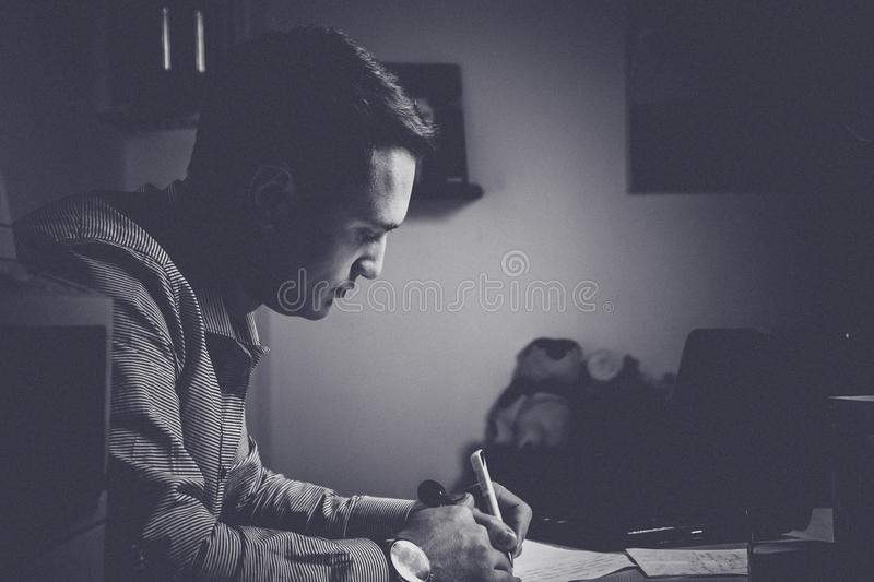 Toned and noisy styled black and white shot. concentrated and tired businessman taking notes in front of the laptop in his office. At late night stock images