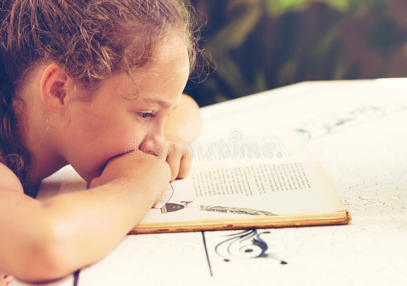 Toned Outdoor portrait of a pretty little girl reading a book stock photo