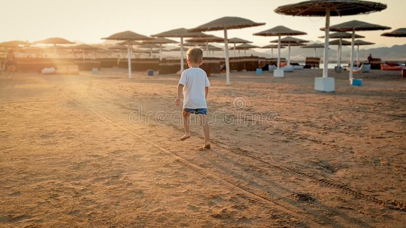 Toned photo of adorable 3 years old toddler boy running on the sea beach towards sunset sun over the shore stock photo