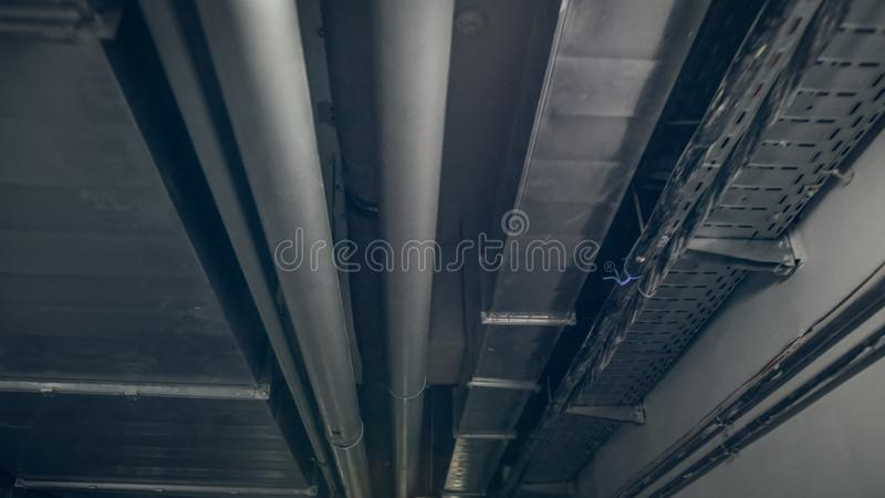 Toned photo of air ventilation pipes and electric wires on ceiling at industrial fabric. ABstract grungy background royalty free stock photo