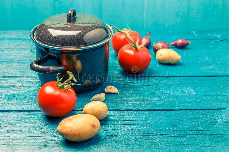 Toned photo of iron pot for soup, tomato, potatoes, onions. On blue wooden background stock photo