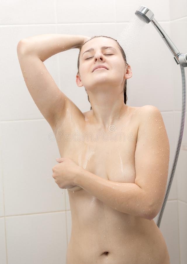 Toned portrait of naked woman with beautiful body showering in bathroom. Toned photo of naked woman with beautiful body showering in bathroom royalty free stock photography