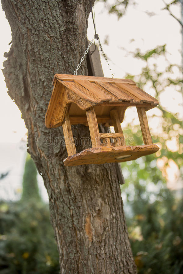 Toned photo of wooden birdhouse hanging on tree at park stock image