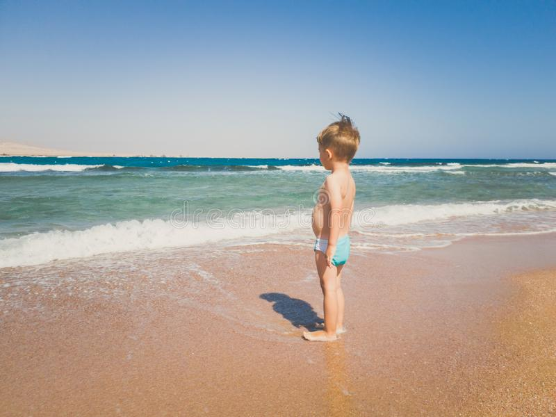 Toned image of 3 years old toddler boy standing on the sea beach and looking at horizon. Child relaxing and having good stock photography