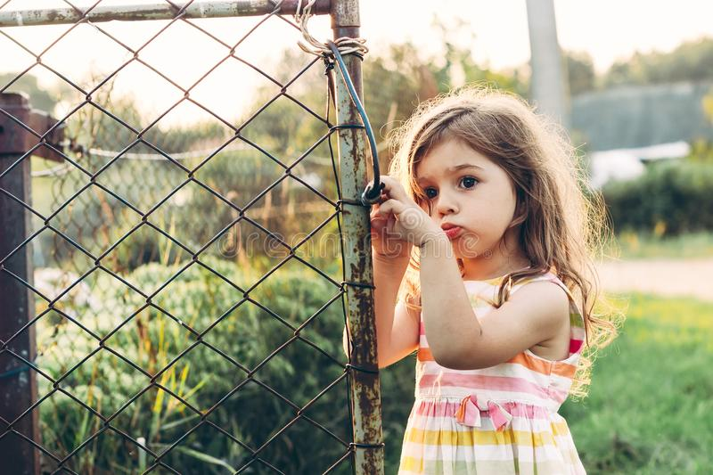 Toned portrait of a Cute little girl looking sad standing near t stock photos
