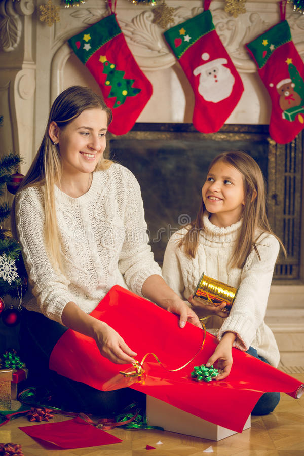 Toned portrait of happy mother and cheerful daughter decorating stock photography