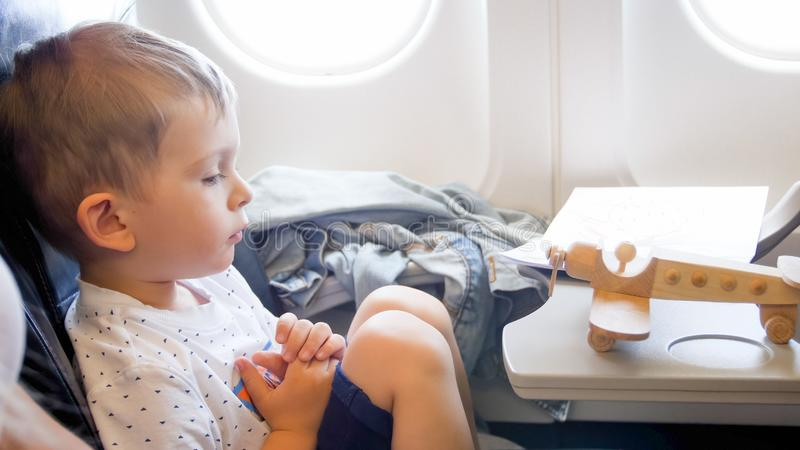 Toned portrait of little boy looking on wooden airplane miniature during long flight royalty free stock photography