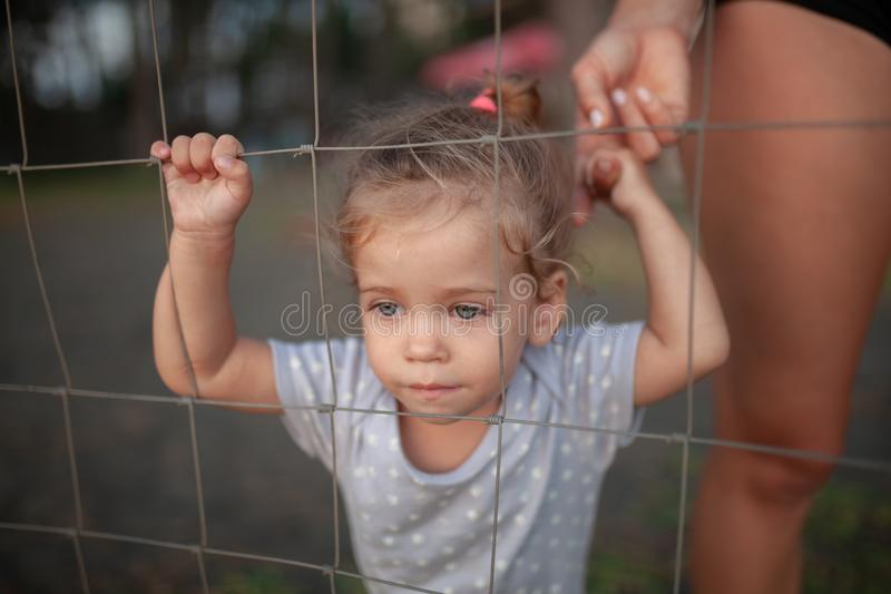 Toned portrait of Sad little girl looks through wire fence royalty free stock photos
