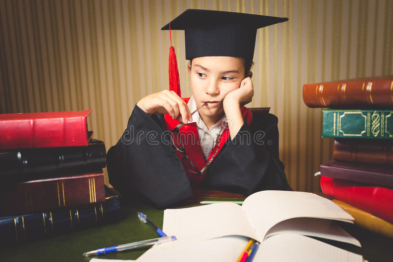 Toned portrait of thoughtful smart girl in graduation hat and go. Wn at desk stock photo