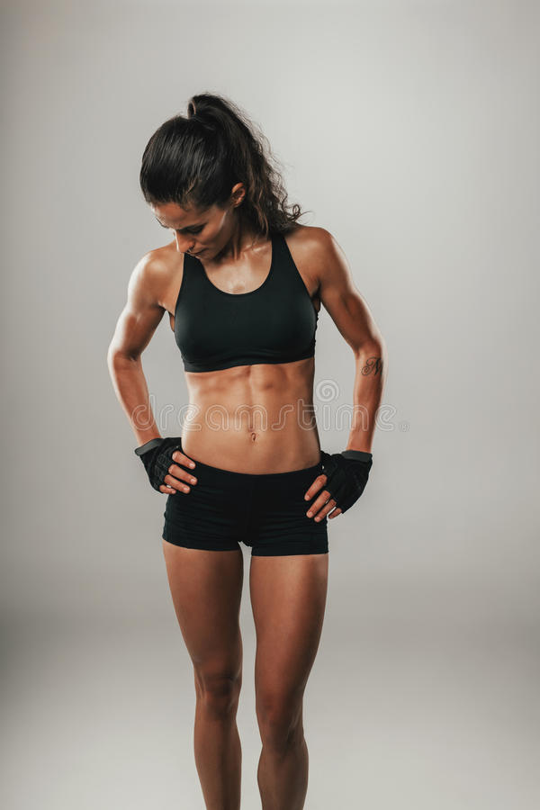 Toned strong young woman in sportswear. Toned strong fit healthy young woman in sportswear standing with her hands on her hips looking down over a grey royalty free stock photo