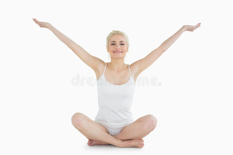 Toned young woman sitting with arms outstretched royalty free stock photos
