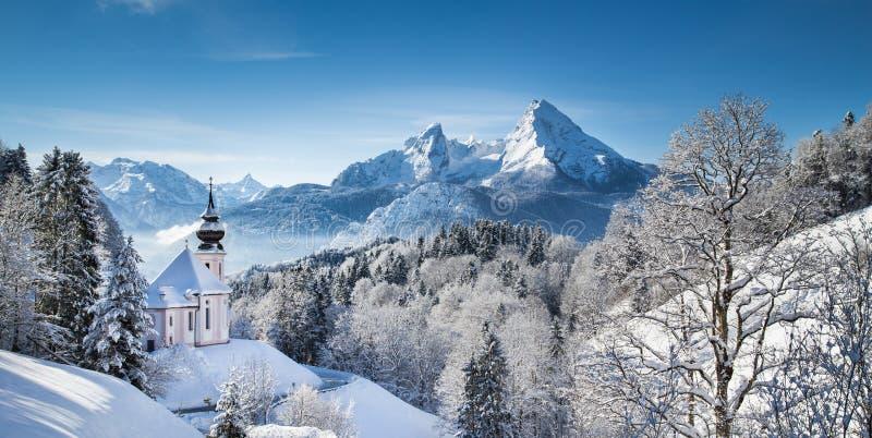 Toneel de winterlandschap in de Alpen met kerk stock foto's